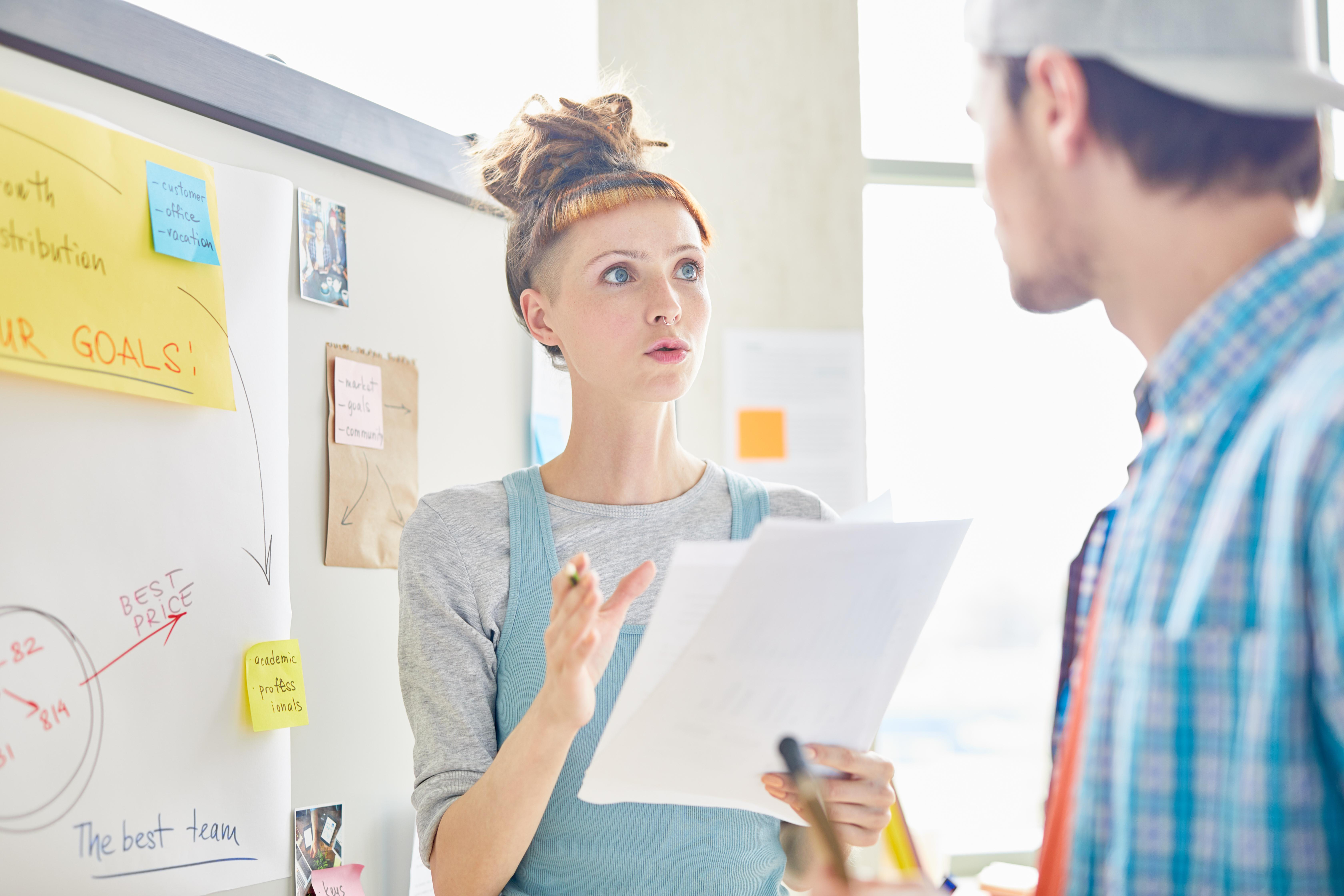Femme sérieuse en marketing avec une coupe de cheveux hipster expliquant les données avec une main gestuelle et l'autre tenant une analyse de marché avec un collègue dans un bureau
