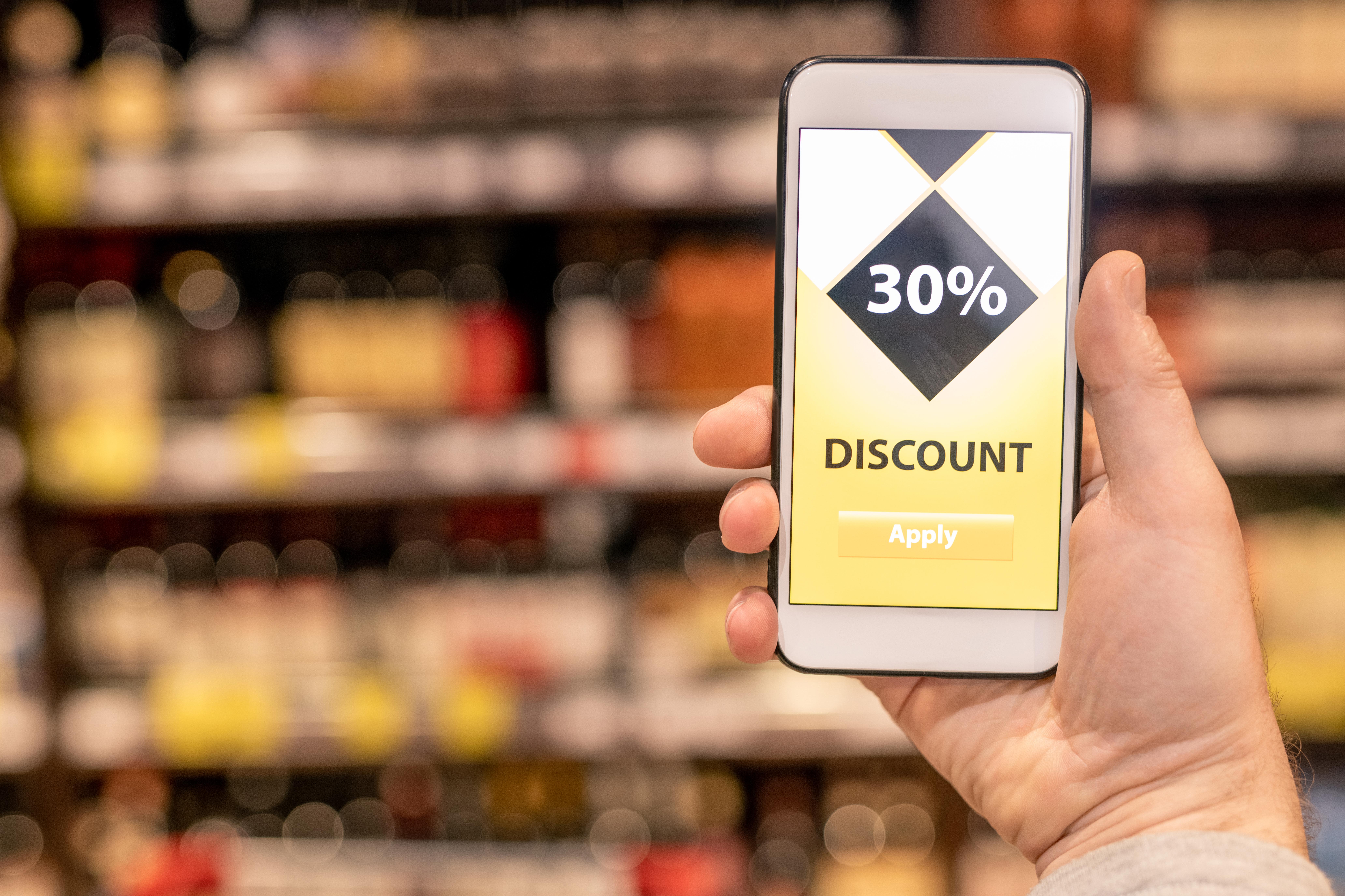 Main tenant un téléphone cellulaire affichant un rabais de 30%