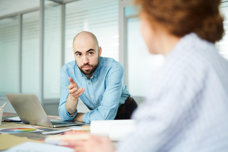 Homme sérieux et chauve accoudé sur une table avec un laptop parlant à une collègue