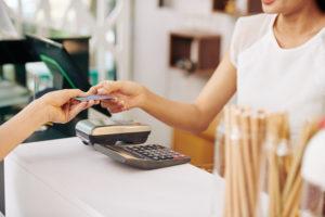 Une femme donne sa carte à uen barista pour payer un café
