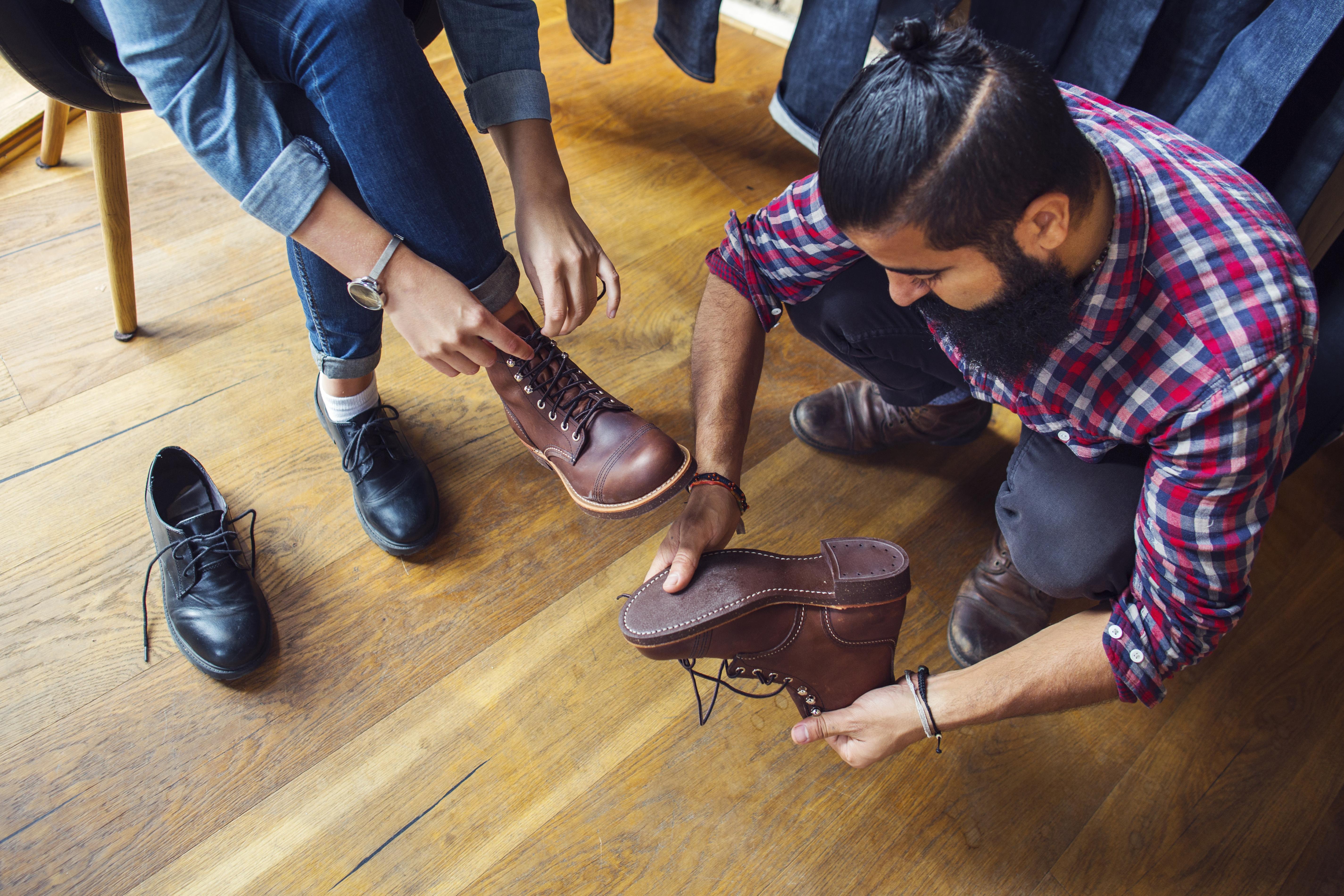 Une femme essaie des souliers dans une boutique avec son ami