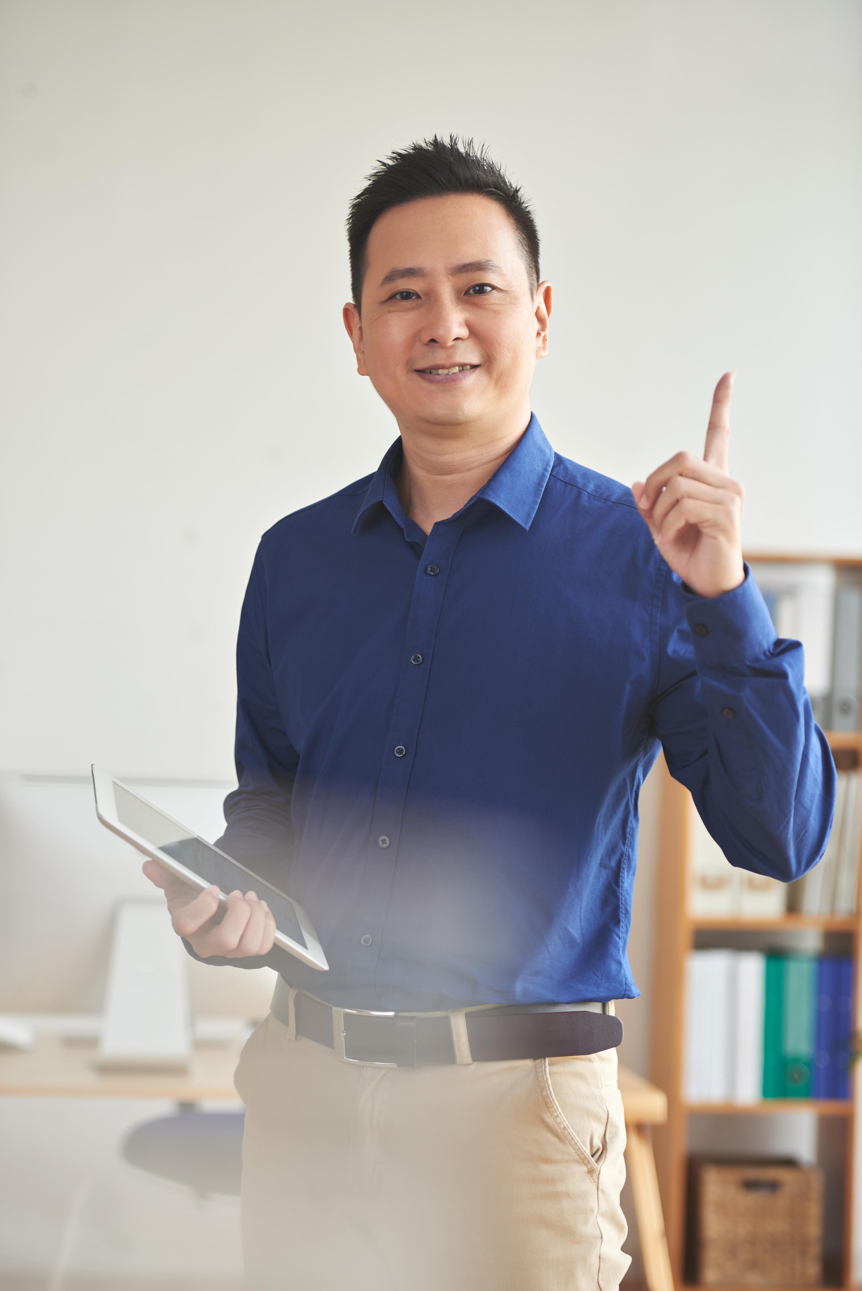Portraint un homme d'affaires asiatique souriant pointant un doigt vers le haut signalant la découverte d'une idée