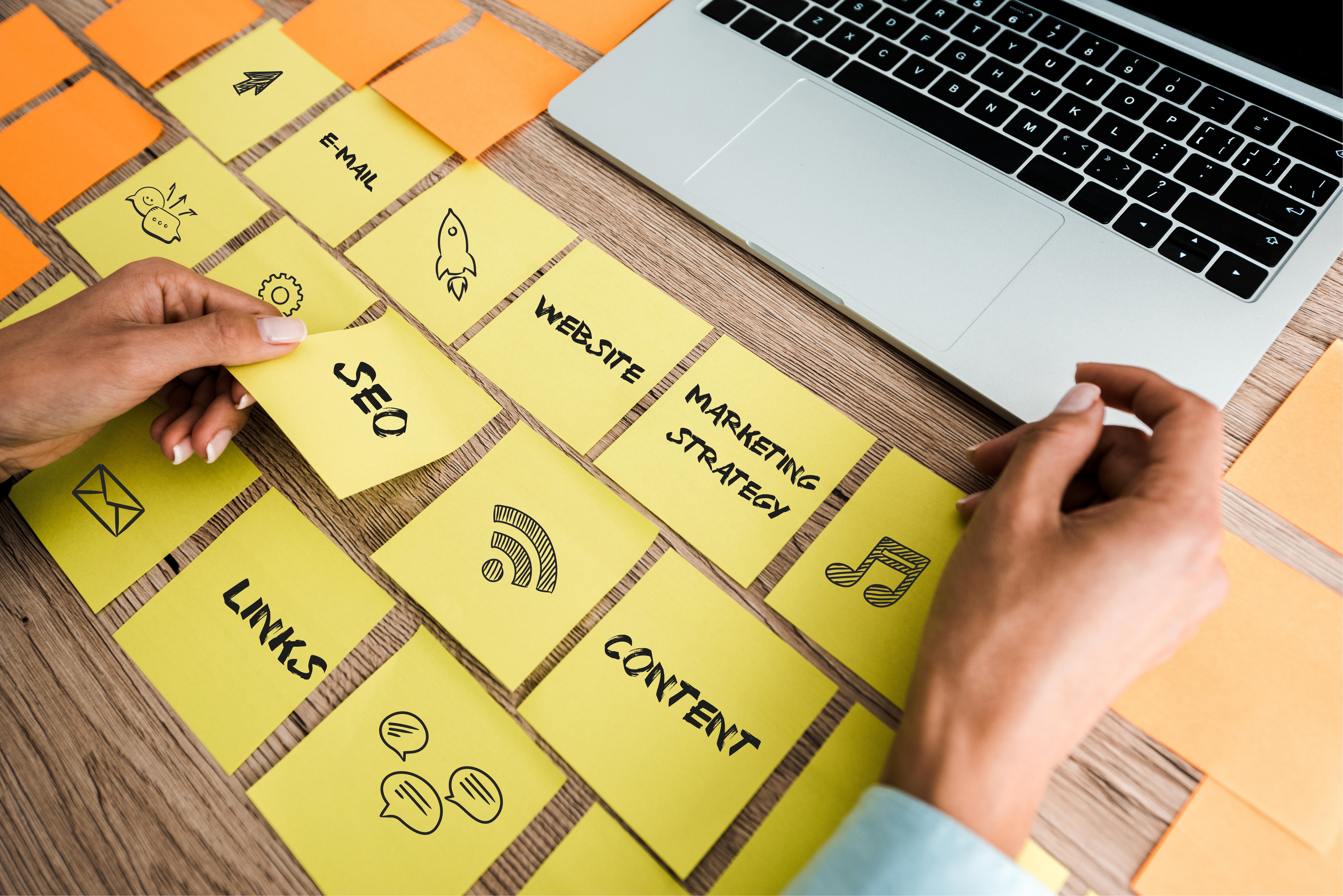 Vue coupée d'une femme qui touche des post-its avec des mots-clés SEO près d'un ordinateur portable